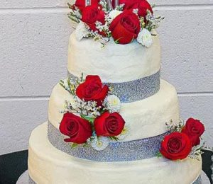 3+tier+white+wedding+cake+with+fresh+red+roses+and+silver+monogram+topper